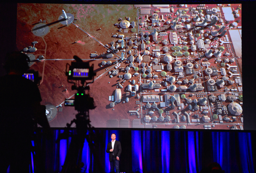 Elon Musk, founder and Chief Executive Officer (CEO) and lead designer of SpaceX, and also CEO and co-founder of Tesla, reacts as a screen displays a depiction of a human colony on the planet Mars during a presentation at the International Astronautical Congress (IAC) in Adelaide, Australia, September 29, 2017. AAP/Morgan Sette/via REUTERS ATTENTION EDITORS - THIS IMAGE WAS PROVIDED BY A THIRD PARTY. NO RESALES. NO ARCHIVE. AUSTRALIA OUT. NEW ZEALAND OUT.